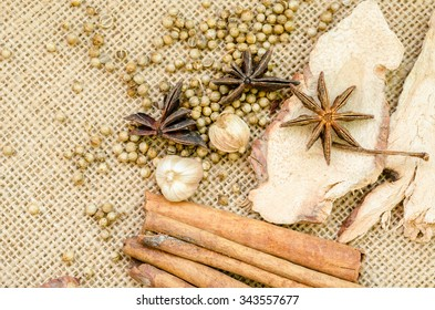 Collection of spices for mulled wine and pastry on sack background.