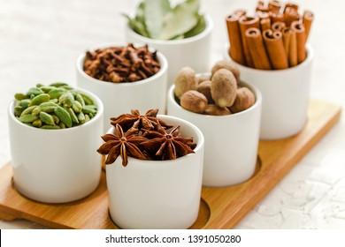 Collection of spices: nutmeg, cardamom, bay leaf, star anise, cinnamon and cloves