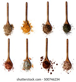 Collection of Spices in Wooden Spoons: Coriander, Curry Powder, Salt with Herbs, Thyme, Salt with Cayenne Pepper, Salt with Petals, Dried Paprika and Salt with Chili isolated on White background