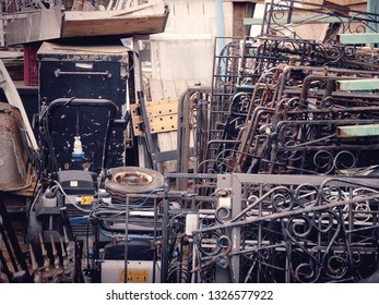 A collection of stacked wrought iron gates and other hardware at a salvage yard in the UK.
