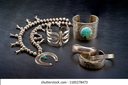 A Collection of Sterling Silver Native American Jewelry. Squash Blossom Necklace, Two Cuff Bracelets, One with a large Turquoise Stone, and Three smaller Bracelets.