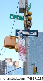 Collection of street signs at West 37th Street and 10th Avenue in New York City, with traffic lights beyond