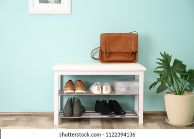 Collection of stylish shoes on rack storage near color wall in room