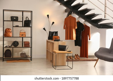 Collection of stylish women's clothes, bags and accessories in luxury boutique