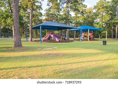 Collection of sun shade playgrounds at grassy public park in Houston, Texas, USA. Safe, comfort covered playground for kids to play all day long. Sail fabric canopy blocks up to 90% harmful UV rays