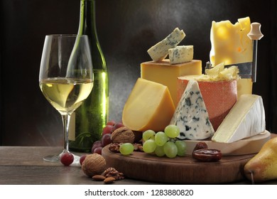 Collection of Swiss, French, Italian and Holland cheeses on a cheese board served with fruit, nuts and white wine