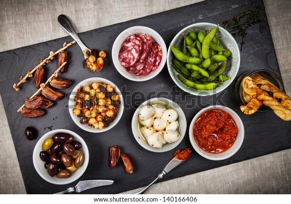Tapas-Speisen wie z.B. Datteln, Kichererbensalat, Salami, frischer Mozzarella, Espamame und Oliven auf einem Schieferbrett.