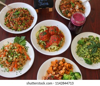 Collection of tasty healthy food items; including lentil meatballs, chickpea salads, chili dishes and a smoothie. Diet food.