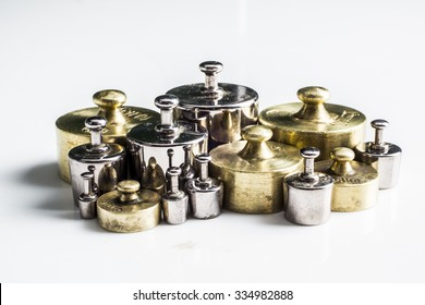 Collection of Thee Vintage Golden And Silver Calibration Weights on White Background