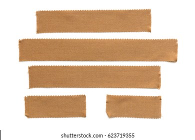 Collection of torn physio tape strips isolated on white.  Brown fabric, for therapeutic strapping.
