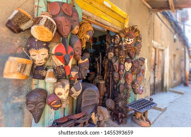 collection of traditional african masks hanging on  an outdoor shop wall in the streets of zanzibar town tanzania