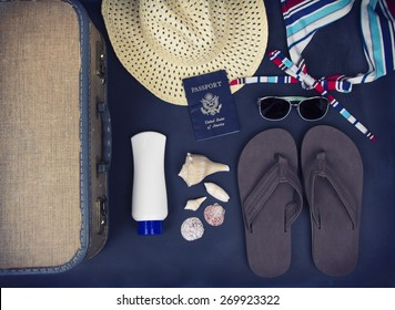 A collection of travel items including suitcase, passport, sandals, sunglasses, swim suit, sunscreen and straw hat on chalkboard background