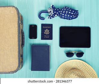 Collection of vacation travel items with a vintage filter on a turquoise background