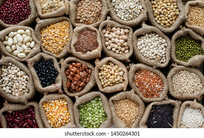 Collection of variety natural dry organic cereal food ingredient in sack bag,for healthy or carbohydrate ood or agricultural product concept,in dark low key tone