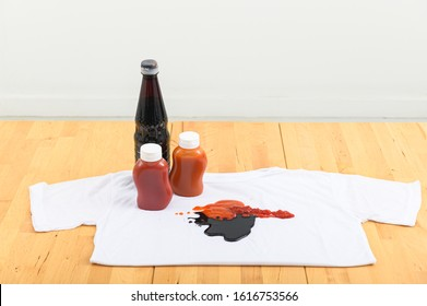 Collection of various food stains from ketchup and black soy sauce on white t shirt.