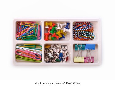 Collection of various pins and paper clips in a plastic tray on white background.