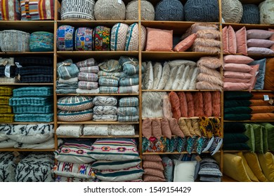 Collection of various throw pillows, baskets and home decorations on a shelf inside storage of store