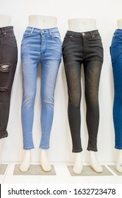 Collection of various types of blue jeans trousers,set of female mannequin in legs of women's jeans of different colors,advertising pants shop,many jeans fashion hanging on mannequin,row of pants