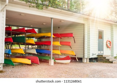 Collection of vibrant colorful plastic recreational canoe and kayaks stored storage rack, side view