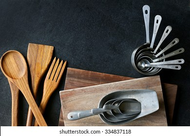 A collection of vintage baking and cooking supplies, wood cutting boards and spoons, and antique silver measuring cups frame a black slate chalkboard background.