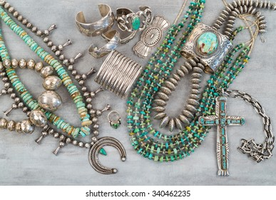 A collection of Vintage Native American Jewelry made of Turquoise and Sterling Silver. Necklaces, cuff bracelets, Squash Blossom and a Silver Cross.