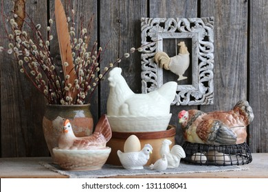 Collection of Vintage Porcelain, Faience, Ceramic Chicken Butter-Dish, Egg cup, Figurine, Branches of Willow in Old Authentic Clay Pot, Weathered Rectangular Frame on Wooden Background , Easter scene