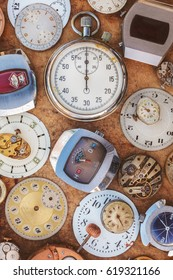 Collection of vintage rusty watches and parts on a brown old wooden background