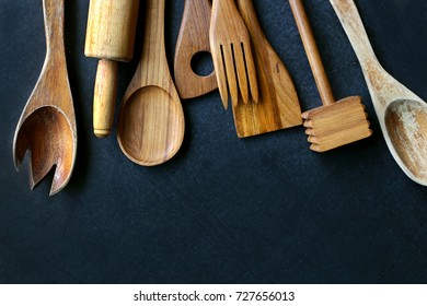A collection of vintage wooden cooking utensils, spoons, rolling pin, masher, spatula, are framing the top border of a black slate chalkboard.