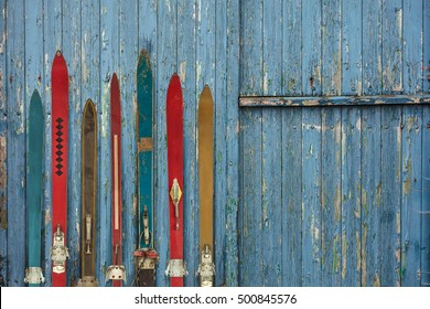 Collection of vintage wooden weathered ski's in front of an old barn