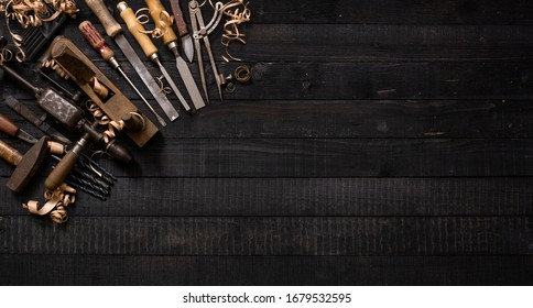 Collection of vintage woodworking tools background on a dark workbench with copy space: carpentry, joinery, craftsmanship and handwork concept, flat lay