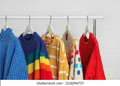 Collection of warm sweaters hanging on rack against white brick wall