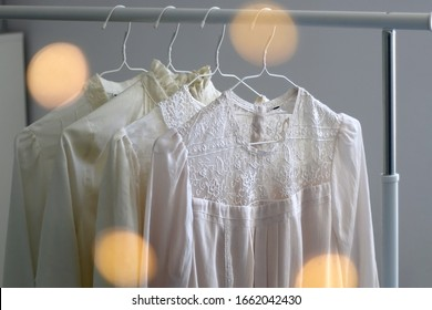 Collection of white feminine blouses on a clothing rack. Selective focus, bokeh lights in the foreground.