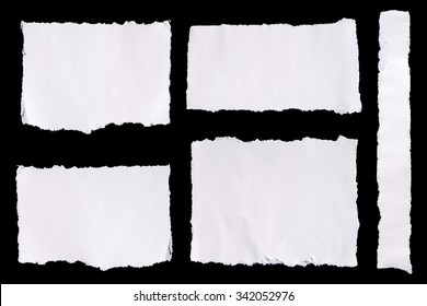 Collection of white ripped pieces of paper on black background