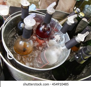 A collection of wine bottles chilling in an ice bucket at an outdoor event.