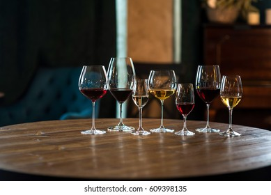 Collection of wine glasses with different wine on wooden table in bar. Life style