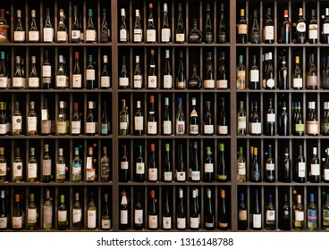 Collection of wines in the store of elite alcohol. Bottles of various wines are beautifully on the rack. Paint effect.