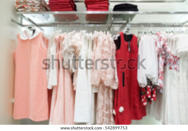 Collection of woman clothes hang on a shelf in the clothes shop, blur background