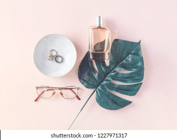 Collection of woman's accessories like jewelry, perfume, glasses next to monstera leaf on pastel pink background. Copy space. Flat lay. Top view