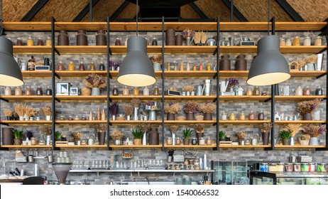 Collection wooden shelf with bottle, plant on counter bar in cafe