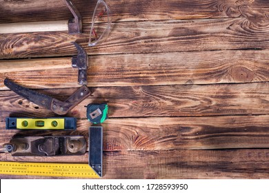 Collection of woodworking tools on a wooden background