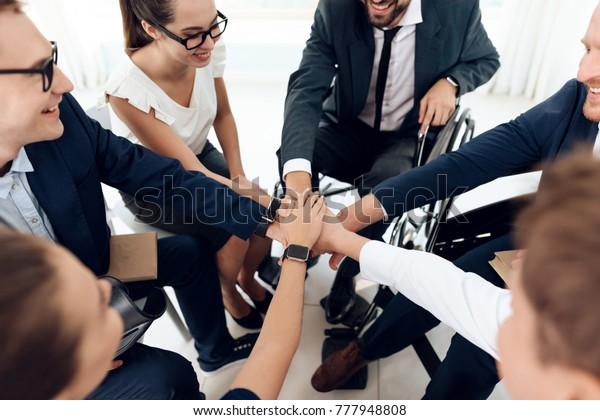 Collective work of full-fledged people and people with disabilities. Persons with disabilities in everyday life. Work disabled businessman. Teamwork with people in wheelchairs.