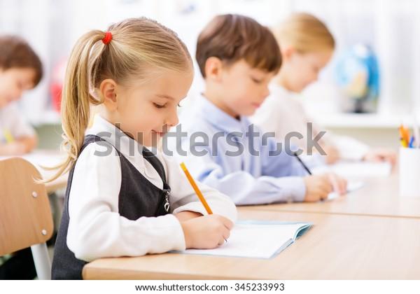 Kollektive Arbeit. Kleine Schüler sind alle damit beschäftigt, in ihren Kopienbüchern zu schreiben.
