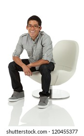College age man sitting on a modern white chair isolated on white
