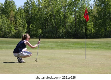 college aged girl surveying her putt on the last hole