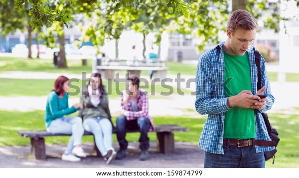 College boy text messaging with blurred students sitting in the park
