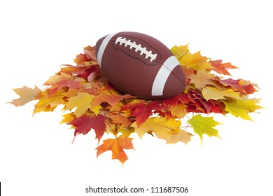 College football on pile of colorful fall leaves isolated on white