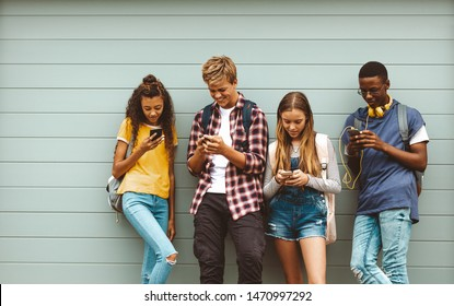 College friends wearing bags using mobile phones standing outdoors. Multiethnic teenage boys and girls standing outdoors against a wall and looking at their mobile phones.