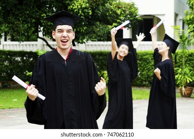 college graduates in graduation gowns standing and smiling. Congratulations to graduates!  shot of cheerful group of three young multi ethnic graduates in black gowns, holding diplomas big laughing