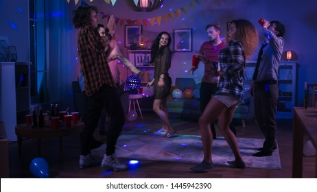 At the College House Party: Diverse Group of Friends Have Fun, Dancing and Socializing. Boys and Girls Dance in the Circle. Disco Neon Strobe Lights Illuminating Room.