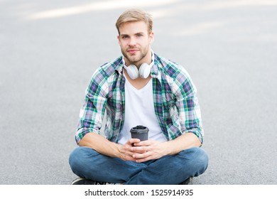 College life. Life balance. Wellbeing and health. Having coffee break. Man sit on ground while drinking coffee. Relax and recharge. Have fun during break. Guy carefree student enjoy coffee outdoors.